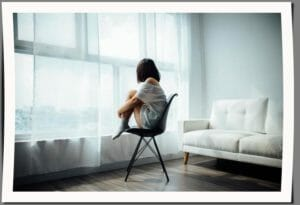 girl sitting in front of window during quarentine