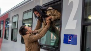 man and woman saying goodbye on train